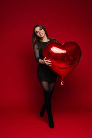 Valentines day celebrating slim young positive girl with template heart shaped balloon on red background, copy space
