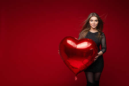 Valentines day holiday, beautiful girl with heart shaped balloon on red background, copy space for festive advertising 스톡 콘텐츠