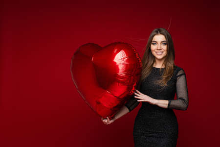 Valentine day celebrating young girl with heart balloon on red background with blank space for advertising 스톡 콘텐츠