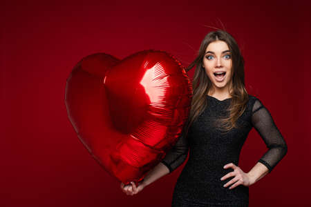 Surprised attractive young girl with template heart shaped balloon on red backdrop, copy space for valentine day ad
