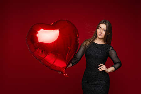 Valentine day celebrating pretty girl in black dress with heart shaped mock up balloon on red background, blank space 스톡 콘텐츠