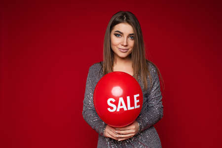 Attractive caucasian long haired young girl holding balloon with text sale smiling posing on red background, copy space 스톡 콘텐츠