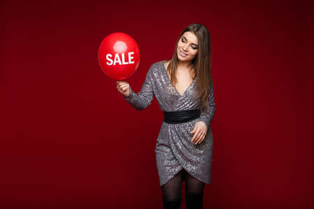 Attractive long haired caucasian girl shows balloon with text sale on red backdrop with blank space for advertisement