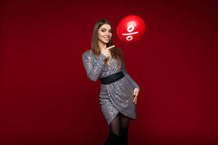 Smiling young girl in festive dress pointing on balloon with per cent sign on red background, sale and discount concept Stockfoto