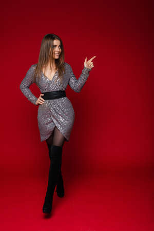 Slim long haired young girl in silver festive dress shows on blank space for advertising on red background