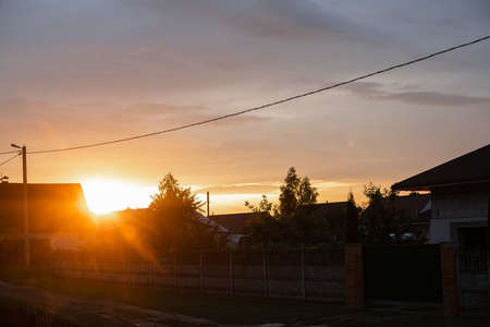 Sunset in countryside. Bright sunlight of the setting sun in the sky over the countryside houses in rural area.