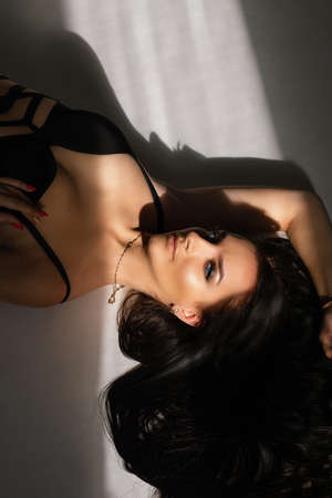 Charming long-haired brunette young female in black lingerie stylish underwear posing on the floor in daylight, top view