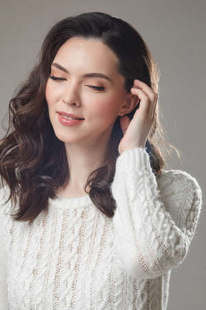 young caucasian model with long dark hair poses for the camera with hand near her face