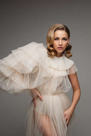 Stylish romantic young beautiful female in dress with pearls collar and perfect hairstyle posing on gray studio backdrop