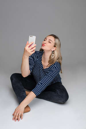 Girl with mobile taking selfie with duck face.