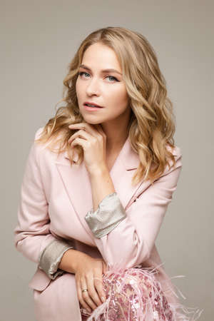 portrait of an attractive female in pink dress with blonde hair poses for the camera with open mouth