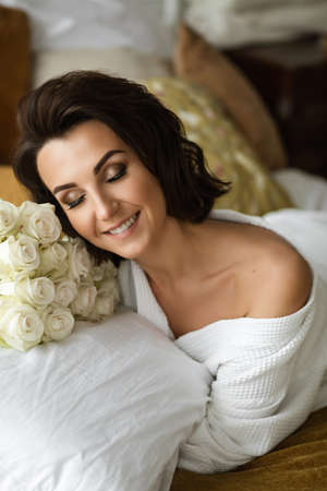 Woman feeling happy and loved while lying with flowers 版權商用圖片