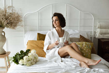 Leisure time of the beautiful lady at home in her bedroom