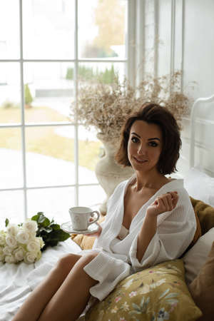 Cheerful young woman relaxing on the pillows with coffee
