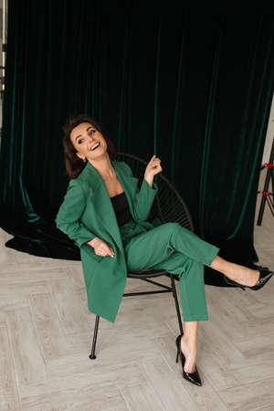 portrait of beautiful female in green suit poses for the camera and smiles