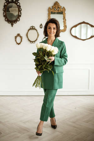 portrait of beautiful female in green suit poses for the camera with a lot of white roses in her hands