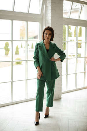 beautiful female in green suit poses for the camera near the big window at home