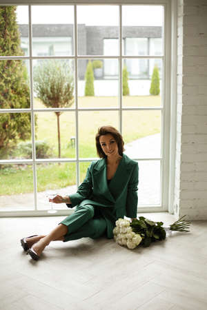beautiful female in green suit poses for the camera with a lot of white roses near the big window at home