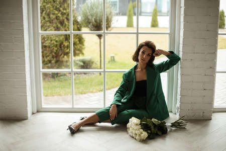 beautiful female in green suit poses for the camera with a lot of white roses near the big window