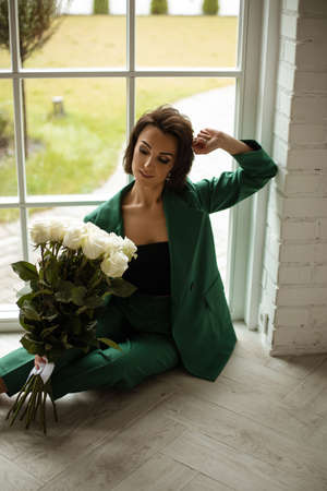 portrait of beautiful female in green suit poses for the camera with a lot of white roses in her hands near the big window 版權商用圖片