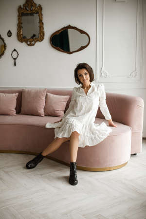 attractive female in white dress poses for the camera on the sofa