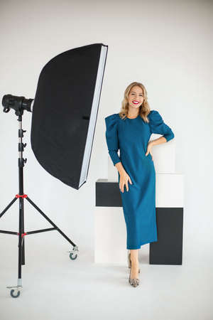 Smiling confident stylish young beautiful female businesswoman in blue dress posing with photographic equipment 版權商用圖片