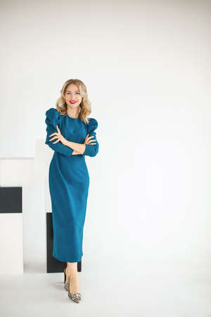 Positive confident stylish 30s young beautiful female businesswoman in blue dress posing on white studio background