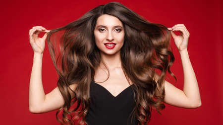 Gorgeous young brunette with ideal long hair on red background. Stock fotó