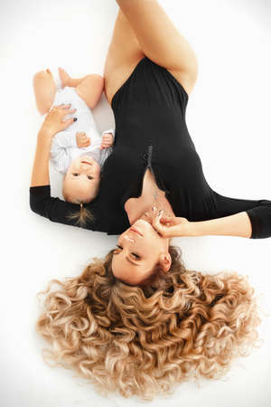 Attractive sexy mother with beautiful hair with baby girl and smiling at camera.