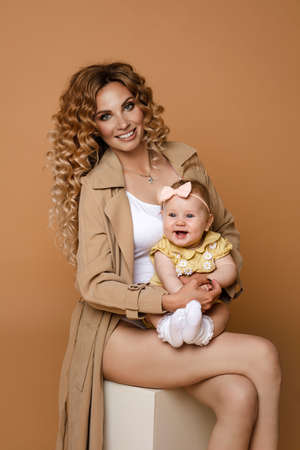 Gorgeous woman in beige trench with a baby daughter and white top holding cute baby daughter in arms sitting on white against peach background. Stok Fotoğraf