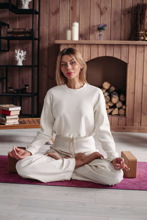 relaxed beautiful caucasian woman with fair hair in white clothes sits on the yoga mat and meditating