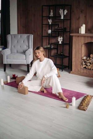 Smiling young girl on mat practicing yoga and meditation in cozy living-room. Female health and wellbeing Stok Fotoğraf