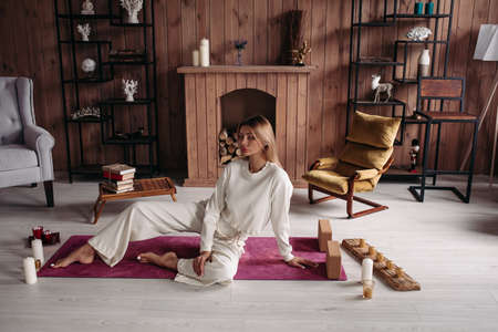relaxed beautiful caucasian woman with fair hair in white clothes lies on the yoga mat with closed eyes