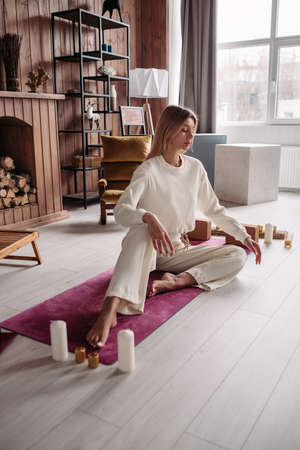 Pretty young calm female meditating relaxing sitting on natural mat in cozy home interior on weekend. Womans wellness