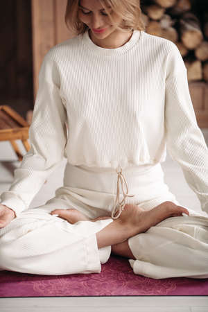 Beautiful young woman enjoying meditation at home
