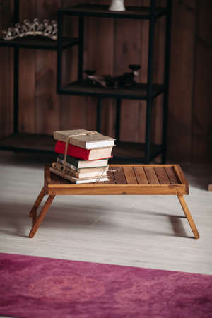 picture of a stack of books on a little wooden table in the bright room