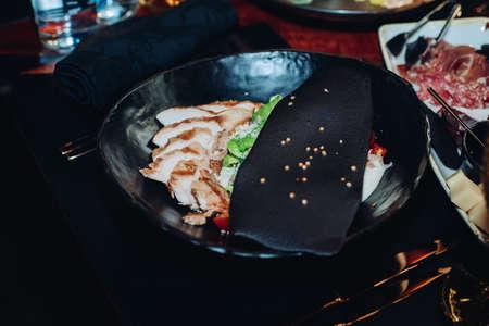 Caesar salad in stylish black bowl.