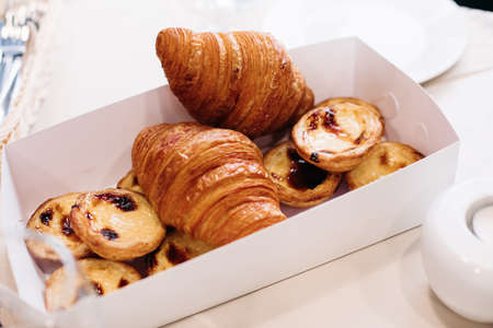 Bakery products, baked sweet croissants, cakes in packaging cardboard box on table for breakfast. Hotel catering