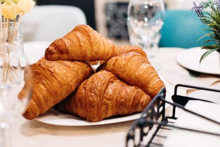 Tasty crisp croissants on a white plate sitting on table