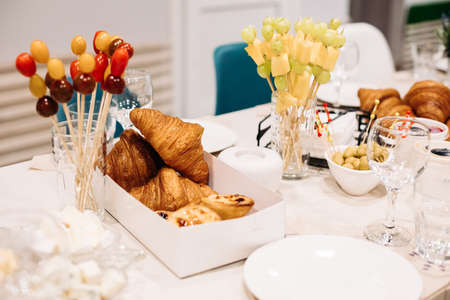 Party catering. Festive dinner table setting with canapes, croissants, different snacks for celebrating event Stok Fotoğraf