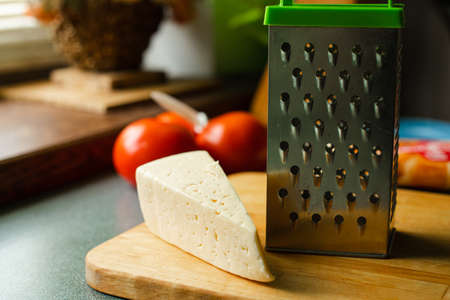 Cheese and grater on wooden board.