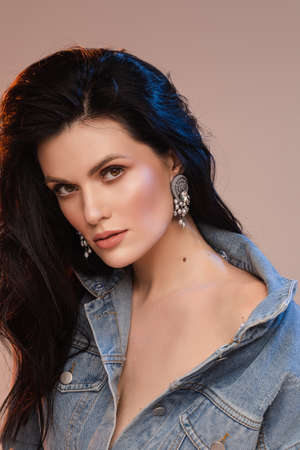 Stylish pretty lady with beautiful earrings in studio