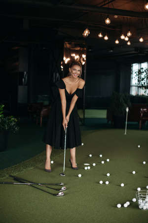 Charming caucasian lady poses for the camera and plays golf, picture isolated on dark blur background Stok Fotoğraf