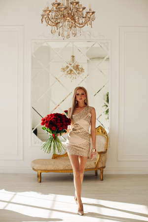 Female fashion model young beautiful blond fit girl holds roses bouquet wearing short festive dress in luxury interior Stok Fotoğraf