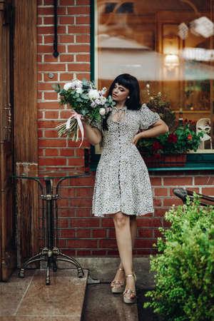 Fashion model with flowers. Standing on step of a restaurant. Zdjęcie Seryjne