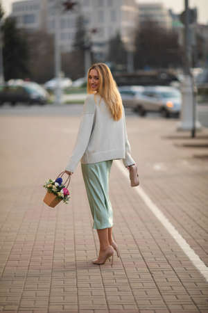 happy young woman walking to the street with a boquet of beautiful flowers in summer