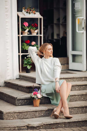 successful young woman sitting near the flower shop and looking aside