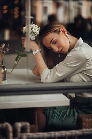 Beautiful stylish romantic young girl wearing evening clothes and jewelry sitting, dreaming with flower in hand in cafe