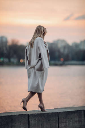 tall woman in shoes and coat walking near the river Zdjęcie Seryjne