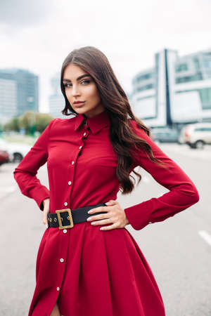 Sexy fashion model in red dress in city.